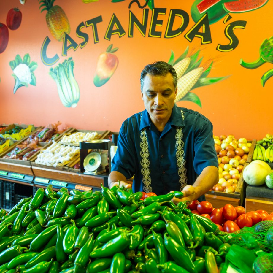 A market stall owner standing by his fruit